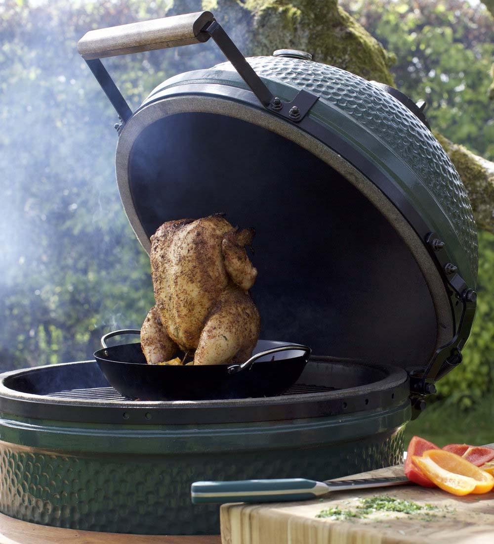 Green big egg bbq met een hele kip op standaard